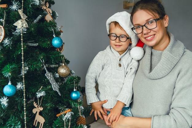 Мама и ее ребенок вместе украшают елку