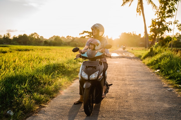 Мама и ее ребенок наслаждаются ездой на мотоцикле