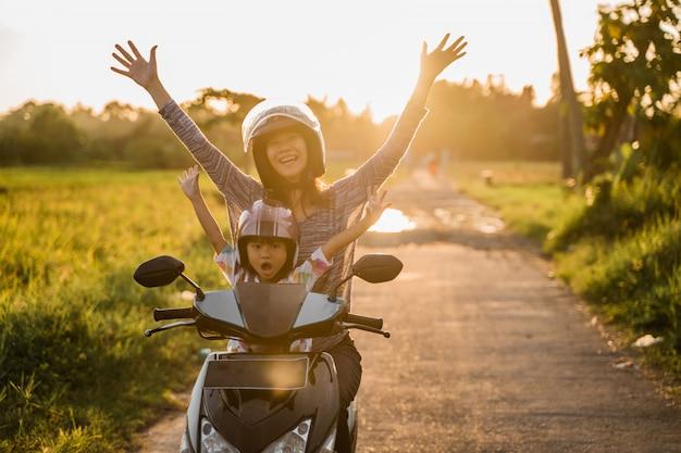 ママと彼女の子供はバイクのスクーターに乗って楽しむ