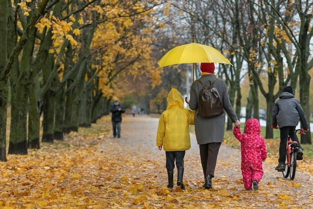 Мама с детьми идут по аллее с падающими желтыми листьями. семейная прогулка с детьми. вид сзади.