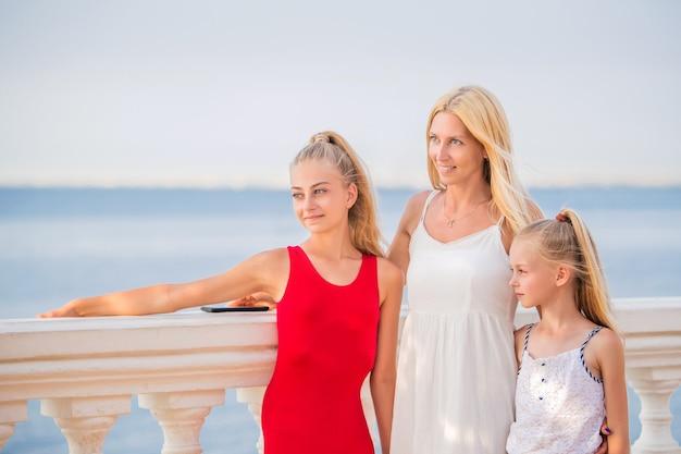 엄마와 그녀의 아이들은 바다에서 여름 휴가를 즐깁니다. 행복한 젊은 백인 어머니와 두 딸은 저녁 태양과 바다를 감상합니다.