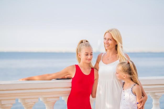 ママと彼女の子供たちは海のそばで夏休みを楽しんでいます。幸せな若い白人の母親と2人の娘は、夕日と海を賞賛します。