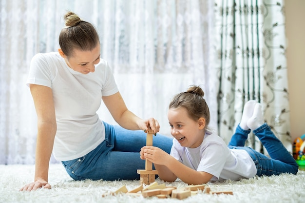 엄마와 딸이 집에서 바닥에 함께 놀고 있습니다. 행복하고 웃는
