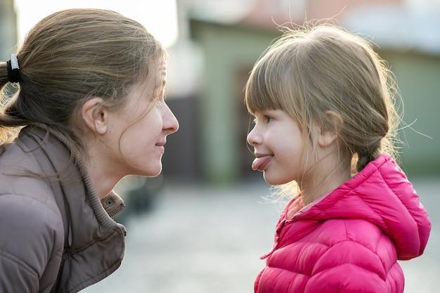 ママと娘の女の子が屋外でお互いに顔を合わせます。