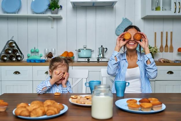 休暇中にキッチンで楽しんでいるママと娘