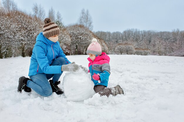 ママと娘は医療用マスクで新鮮な空気の中で遊んで雪だるまを雪だるまから作ります