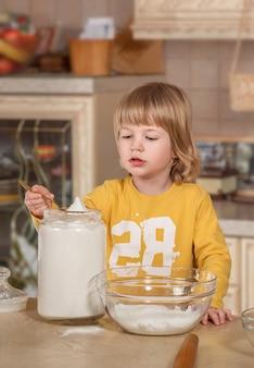 ママと彼女の小さな子供は台所で料理をしています。
