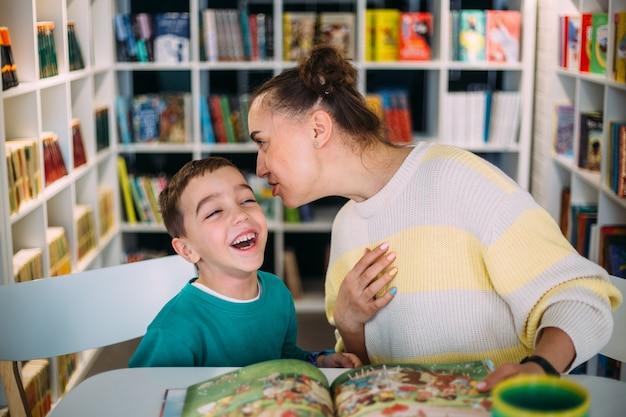 엄마와 그녀의 어린 아이 미취학 아동이 함께 어린이 책을 읽었습니다.