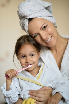 Мама и ее маленькая дочь чистят зубы