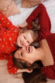 Мама и ее маленькая дочь лежат на кровати лицом друг к другу, они счастливы