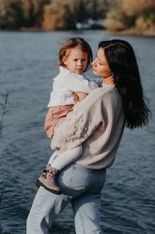 Мама и ее маленькая дочь стоят на берегу озера в осеннем парке. мама держит ребенка на руках. вид сзади.