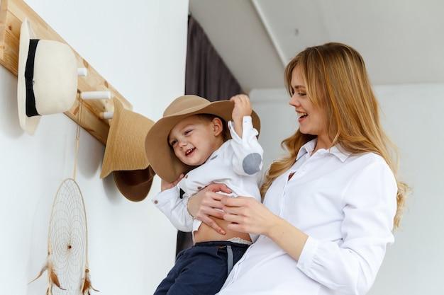엄마와 그녀의 어린 아들은 다른 모자를 쓰고 재미 있습니다.