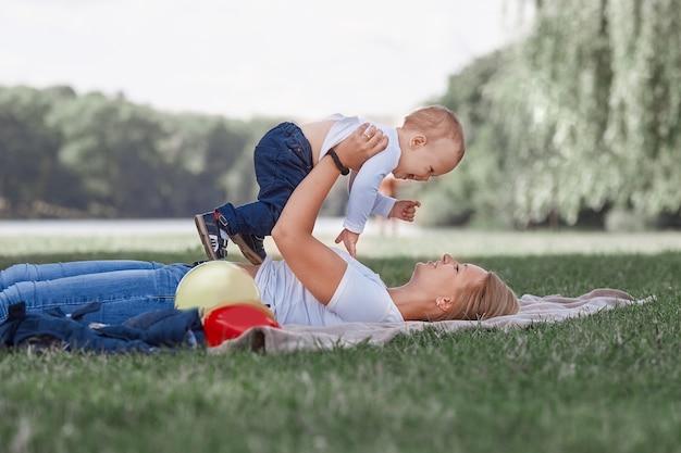 芝生の上で横になって遊んでいるお母さんと彼女の幼い息子
