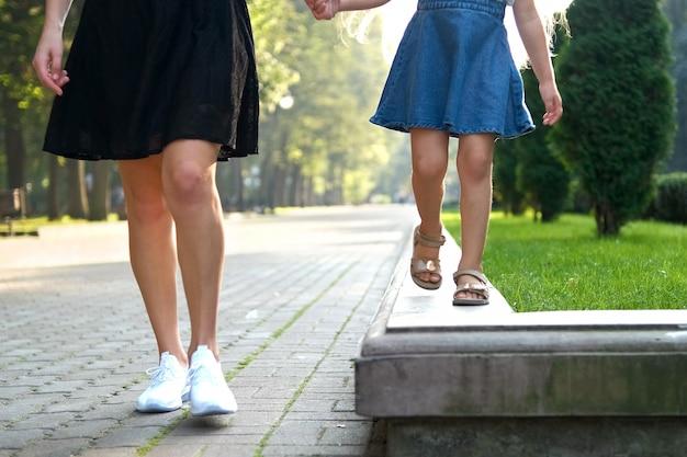 Мама и ее маленькая дочь с длинными волосами гуляют вместе, взявшись за руки в летнем парке.