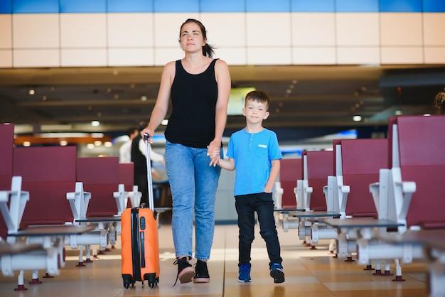 Мама и ее сын в аэропорту с чемоданом