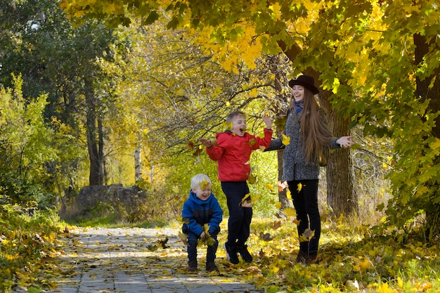 ママと彼女の息子たちは葉を投げます。秋の公園。