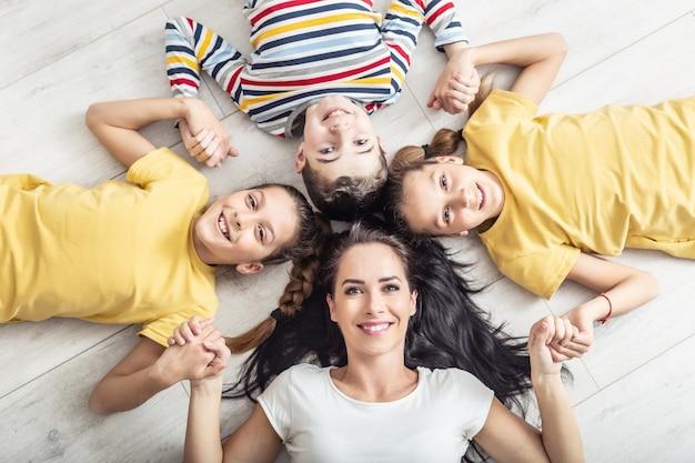 Мама и трое ее детей держатся за руки, лежа на полу и глядя в камеру.