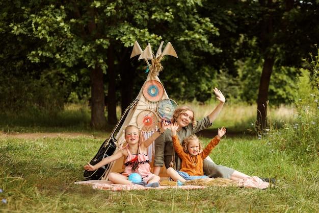 ママと彼女の2人の娘は、公園のウィグワム装飾の隣に座って手を振っています。