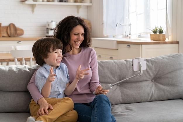 Мама и ребенок держат телефон на селфи-палке для видеозвонка