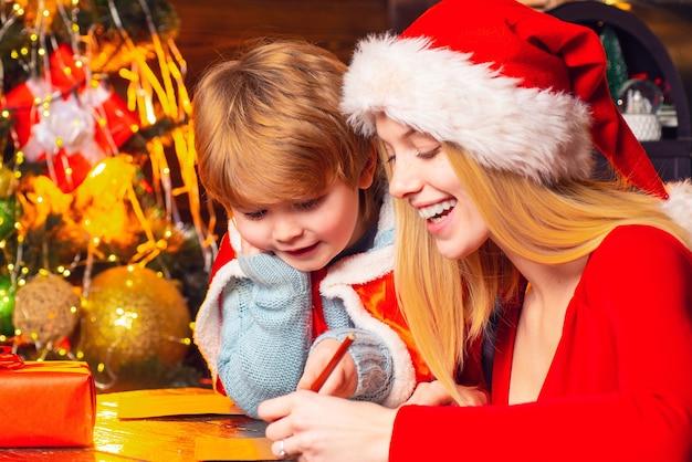 엄마와 아이가 크리스마스 이브에 함께 놀아요. 행복한 가족. 가족 휴가. 산타 클로스가 온다. 어머니와 어린 아이 소년 사랑스러운 친절한 가족 재미. 가족 집 크리스마스 트리에서 재미입니다.