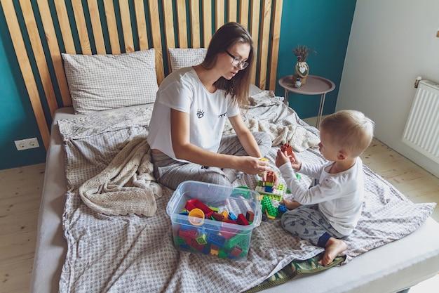 Мама и ребенок вместе играют в спальне на кровати из пластиковых блоков