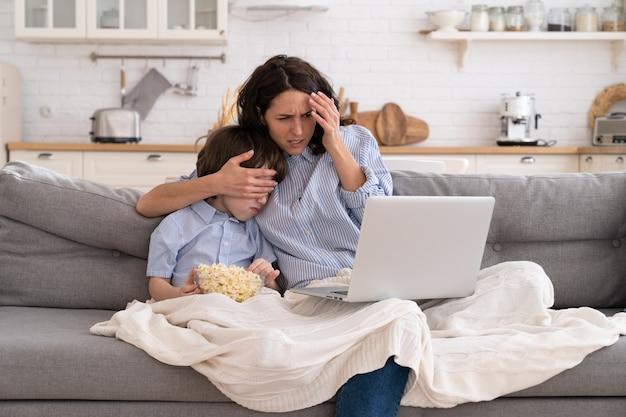Мама и сын с миской попкорна смотрят страшный фильм, закрыв глаза, сидя на диване у себя дома