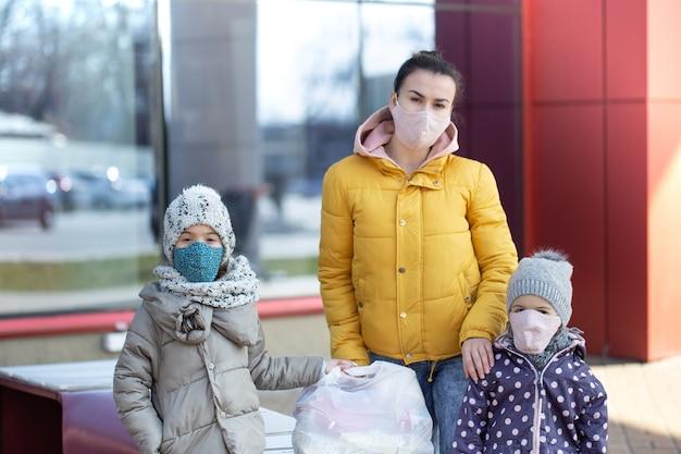 엄마와 아이들은 검역 기간 동안 가면을 쓰고 매장 근처의 거리에 서 있습니다.
