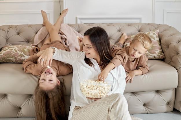 Мама и дети едят попкорн дома в выходной. женщина мальчик и девочка отдыхают на диване и обнимаются