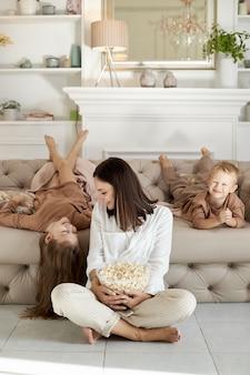 ママと子供たちは休日に家でポップコーンを食べます。男の子と女の子の女性がソファでリラックスして抱きしめます