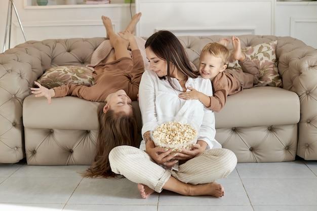 Мама и дети едят попкорн дома в выходной.