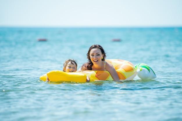 엄마와 3 살짜리 딸이 노란색 풍선 원과 키스로 바다에서 함께 수영합니다.