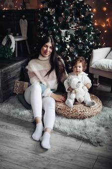 ママとかわいい娘が家のchriatmasの木の隣に座っています