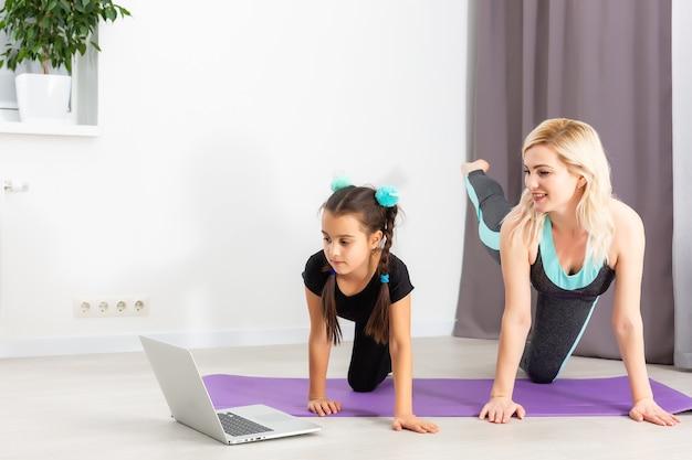 엄마와 어린 딸이 집에 있는 매트에서 체조를 하고 있습니다. 그들은 요가를 합니다. 그들은 행복한 가족이 있기 때문에 재미있습니다. 그들은 노트북을보고 포즈.