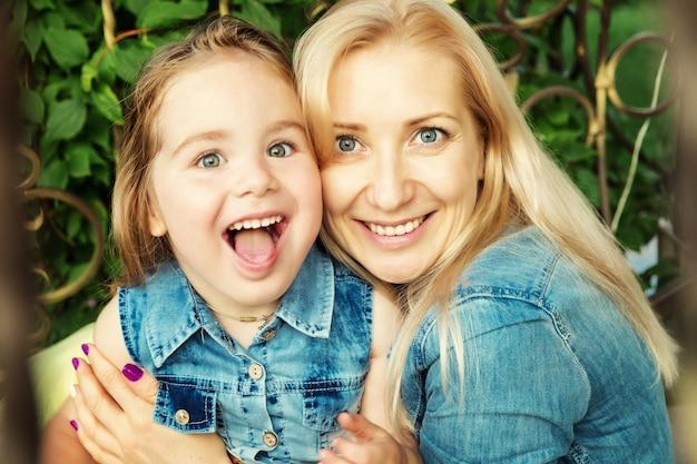 ママと小さな娘の抱擁と笑い