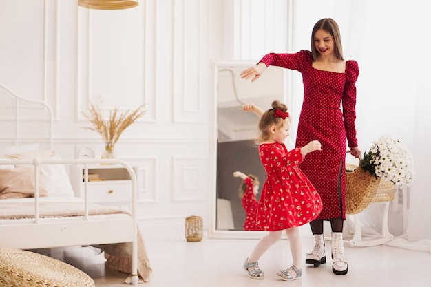 Мама и дочка в красных платьях в яркой спальне в скандинавском стиле. счастливая семья. мама держит букет ромашек - весеннее фото