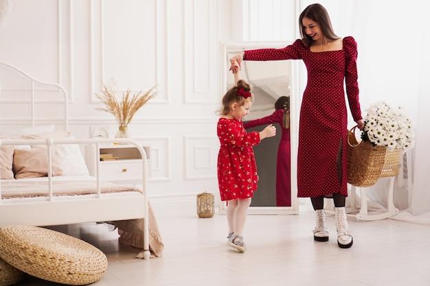 Мама и дочка в красных платьях в яркой спальне