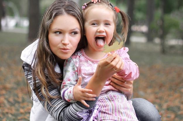 秋の日に公園でママと幼い娘。
