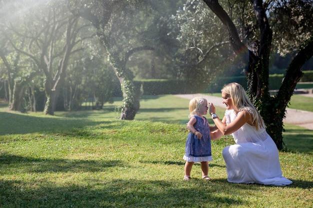 Мама и дочка летом в парке гуляют под струями воды радость счастьяxa