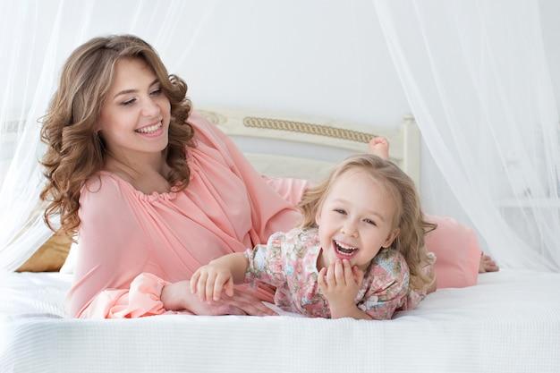 ママと幼い娘がベッドに横になって笑う
