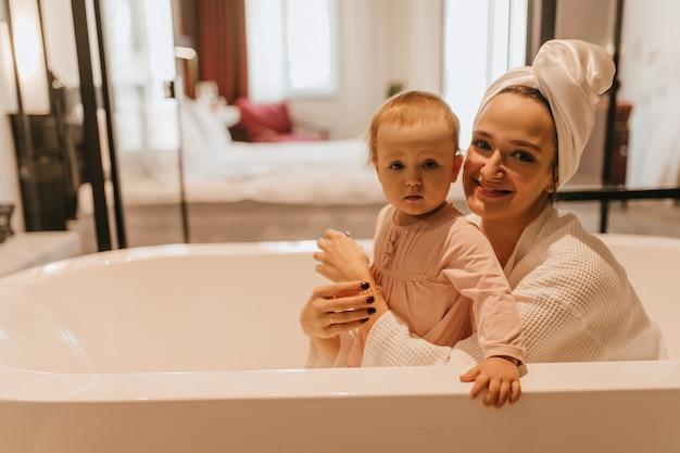흰색 욕조에 앉아있는 동안 엄마와 어린 딸이 미소로 카메라를 봅니다.