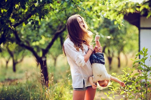 Мама и маленькая девочка веселятся в саду