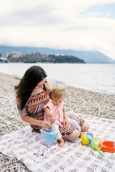엄마와 어린 소녀는 자갈 해변의 침대보에 앉아 장난감을 가지고 노는