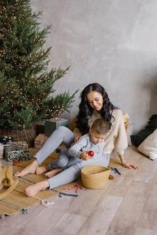 ママと幼い息子が居間のクリスマスツリーの近くの床で遊ぶ
