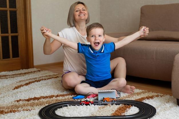 Мама и маленький сын играют в гонки на ковре дома, веселятся и обнимаются.