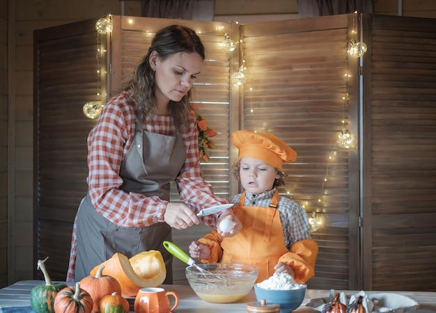 ママと幼い息子は感謝祭のためにカボチャのパイを準備します。家族の休日と伝統の概念