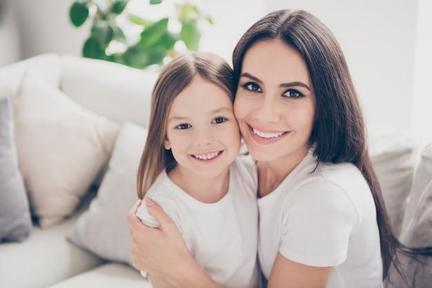 ママと小さな娘が部屋のアパートで抱き合う