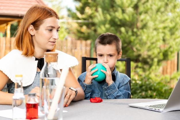 Мама и сын проводят дома физические эксперименты. опыт с ребенком о том, какой из шаров пустой или с водой, быстрее лопнет от огня. шаг 1