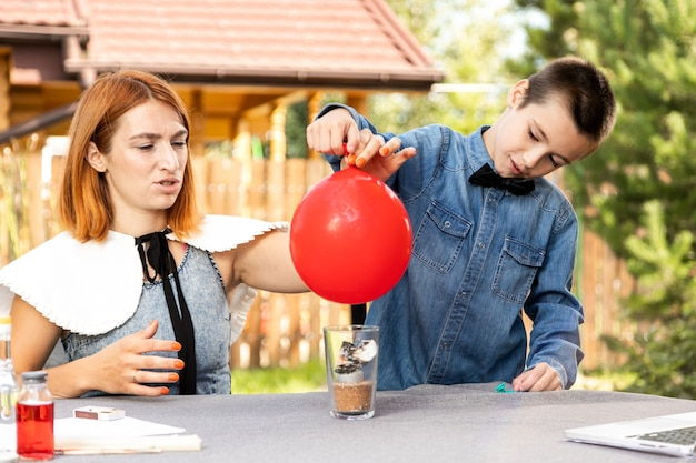 엄마와 아들은 집에서 신체 실험을 하고 있습니다. 공 중 어느 것이 비어 있는지 물이 있으면 불에서 더 빨리 터질 것인지에 대한 어린이의 경험. 4단계