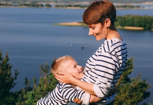 ママと息子は大きな川の背景を抱きしめている