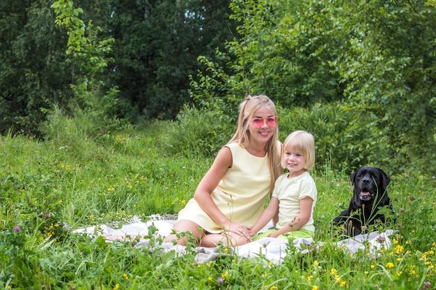 엄마와 아들은 공원에서 담요에 포옹하고 있습니다. 클로즈업 초상화. 핑크 선글라스에 여자입니다. 큰 검은 개가 근처에 있습니다.